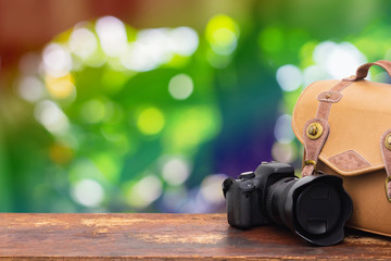 Digital camera and camera bag on an old brown wooden table.Abstract nature green boke background.