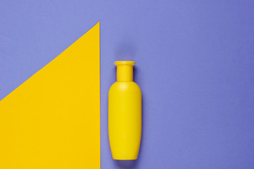 Bottle of liquid soap on colored paper background with geometric shapes. Shower gel, shampoo. Pop...