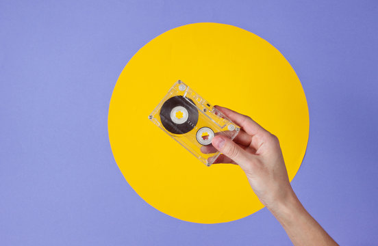 Female hand holding audio cassette on purple background with yellow circle