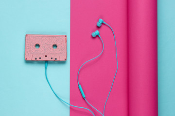 Audio cassette and earphones on wrapped paper background. Pastel color trend, minimalistic retro 80s still life. Top view