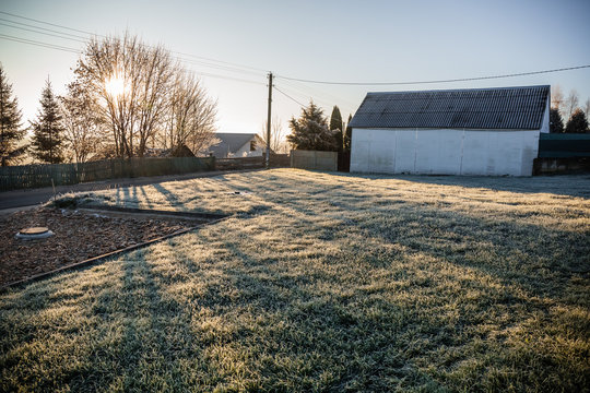 A plot of land with a lawn for the construction of a house or territory for grazing farm animals in frosty sunny morning. May be cut to banner or wallpaper with copy space.
