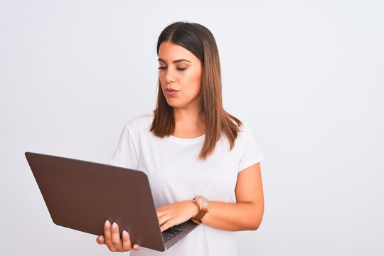 Beautiful young woman working using computer laptop over white background Relaxed with serious expression on face. Simple and natural looking at the camera.