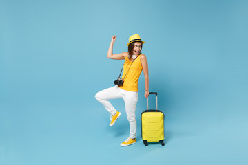 Obraz Traveler tourist woman in yellow casual clothes, hat with suitcase photo camera isolated on blue background. Female passenger traveling abroad to travel on weekends getaway. Air flight journey concept - fototapety do salonu