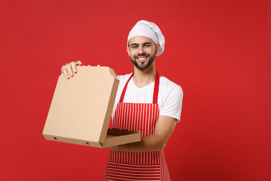 Smiling young bearded male chef cook or baker man in striped apron toque chefs hat posing isolated on red background. Cooking food concept. Mock up copy space. Hold italian pizza in cardboard flatbox.