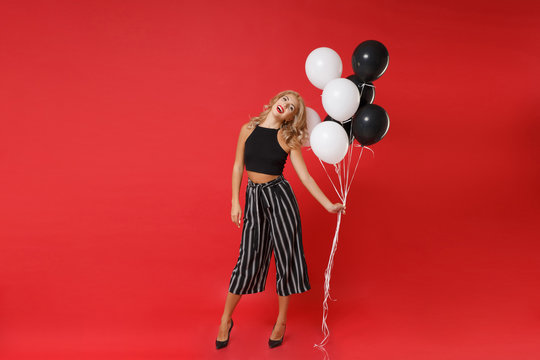 Cheerful funny young woman girl in black clothes posing isolated on red background in studio. Happy New Year 2020 birthday holiday party concept. Mock up copy space. Celebrating, holding air balloons.