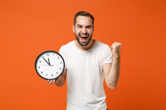 Happy young man in casual white t-shirt posing isolated on bright orange background studio portrait. People sincere emotions lifestyle concept. Mock up copy space. Holding clock, doing winner gesture.