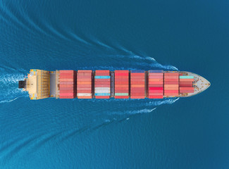 Aerial top view container cargo ship full speed with beautiful wave pattern for business logistics, import export, shipping or transportation.