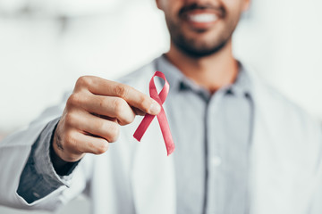 Obraz Red ribbon for HIV illness awareness in doctor's hand, 1 December World AIDS Day concept. - fototapety do salonu