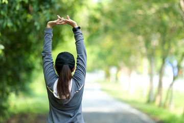 Keuken foto achterwand Jogging Healthy woman warming up stretching her arms. Asian runner woman workout before fitness and jogging session on the road nature park. Healthy and Lifestyle Concept
