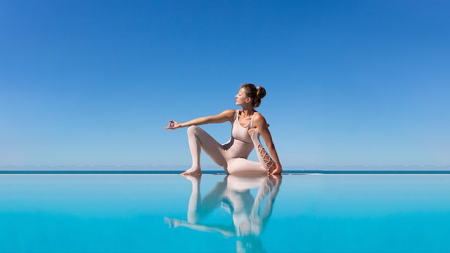 Beautiful athletic slim woman working out outdoors doing yoga asana on the edge of a blue water pool against the sky while relaxing at a spa resort. Copyspace