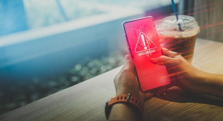 Malware,cyber crime and Personal Data Protection Act concept.Close up hand of anonymous hacker and uses a malware with mobile phone to hack password the money from Bank accounts and personal data.