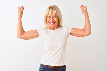 Middle age woman wearing casual t-shirt standing over isolated white background showing arms...