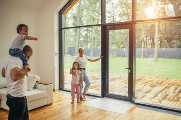 Parents with children look at panoramic window together, relaxing together, spending time at home. Modern house interior