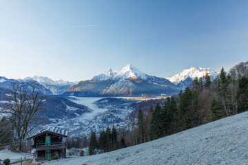 Berchtesgaden and Mountain Watzmann at sunrise in winter with small hut and fog in valley