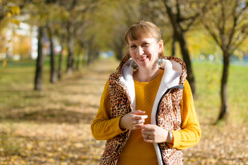 Portrait of a beautiful Russian woman 40 years old, in the autumn park.