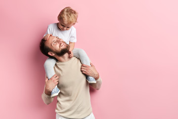 young father having nice time with his son. close up portrait, isolated puk background,