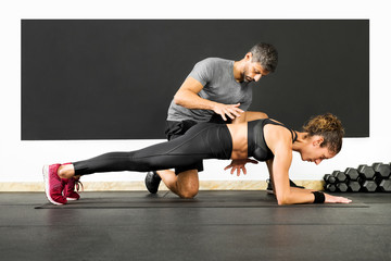 Woman doing plank with the help of a trainer