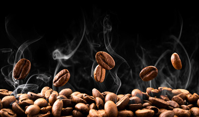 Foto op Aluminium Koffiebonen Coffee beans fall in smoke on a black background. Roasting coffee