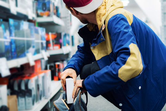 close up consumer  thief's hands putting the new gadget in the pocket in the store