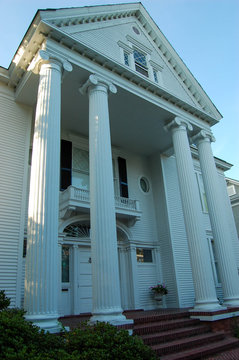 Old plantation house with massive columns on the front porch. White house with black shutters.