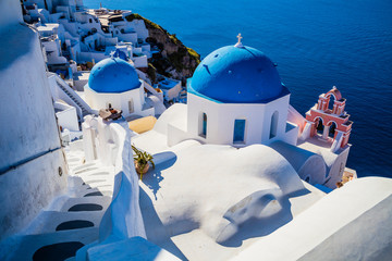 Poster Santorini Traditional white architecture and greek orthodox churches with blue domes over the Caldera in Aegean