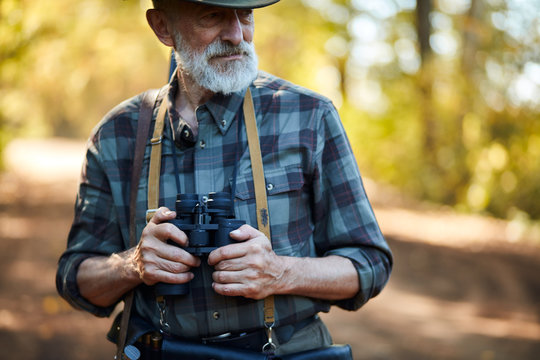 man with grey beard holding binoculars during hunting in autumn forest, looking away. Road background