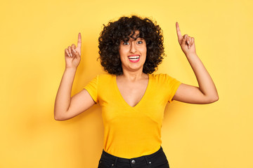 Young arab woman with curly hair wearing t-shirt standing over isolated yellow background smiling amazed and surprised and pointing up with fingers and raised arms.