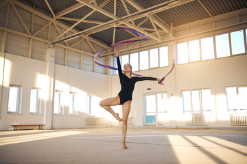 Talented beautiful girl training in comfortable bright room, stands in Sur le cou-de-pied pose, raises hand with long ribbon high, looks up, bottom shot, gymnastics concept