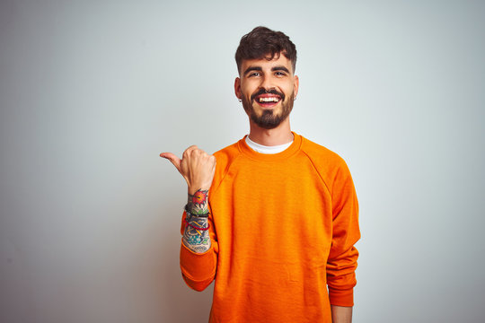 Young man with tattoo wearing orange sweater standing over isolated white background smiling with happy face looking and pointing to the side with thumb up.