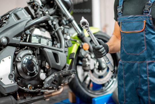 Mechanic repairing motorcycle at the workshop