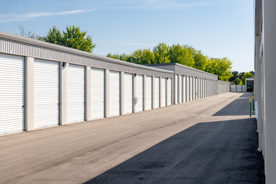 Row of storage units with garage doors with trees