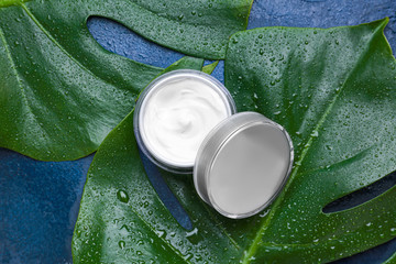 Jar of cosmetic cream with tropical leaves on color background, top view