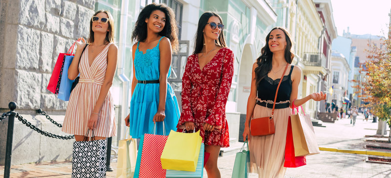 Big city life. Three brunettes and one blonde are walking along the city streets after shopping, carrying lots of bright paper bags and chatting happily.