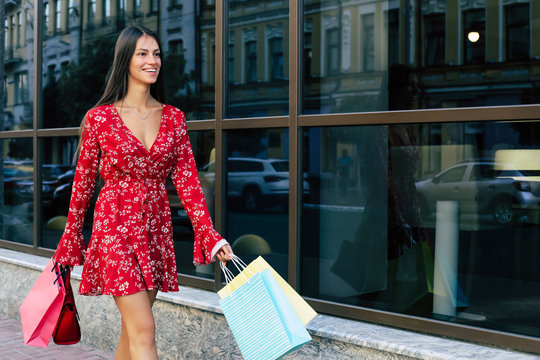 Shop till you drop. Young gorgeous lady is walking along the street in a red dress with floral pattern, carrying several shopping bags, laughing and looking forward.