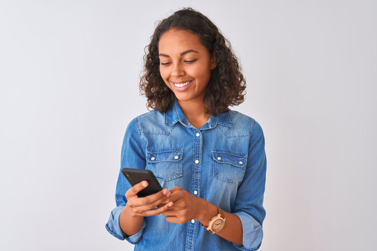 Young brazilian woman using smartphone standing over isolated white background with a happy face standing and smiling with a confident smile showing teeth