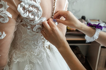 The bride is helped to wear a dress. The concept of marriage, family relationships, wedding paraphernalia.