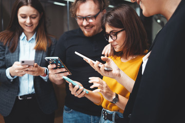 Happy business people standing together and hold in hand modern smartphone. Positive group of office employees meeting at workplace using phone