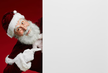 Portrait of classic Santa Claus smiling gleefully at camera while pointing at blank white sign, copy space