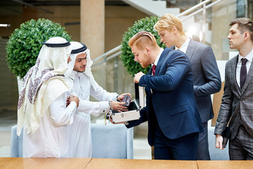 Sheikhs in white suit look at new modern technology in case