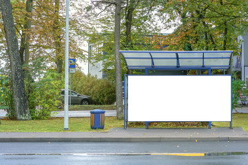 empty glass bus stop with blank white billboard near road in city mock-up