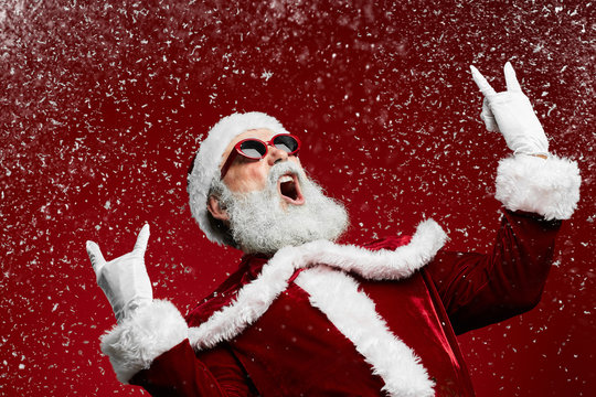 Waist up portrait of cool rock Santa roaring over red background with snow falling, copy space