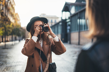 Outdoor smiling lifestyle portrait of pretty young woman having fun in sun city Europe autumn with camera travel photo of photographer Making pictures in glasses and hat with girlfriends Fotobehang