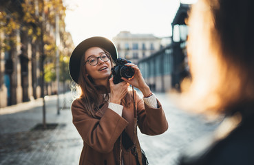 Photographer with retro camera take photo model girlfriend. Tourist smile girl in hat travels in Barcelona holiday with traveler friend. Sunlight flare street in europe. Photoshoot concept in city.