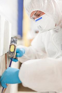 Asbestos surveyor taking a sample of building material