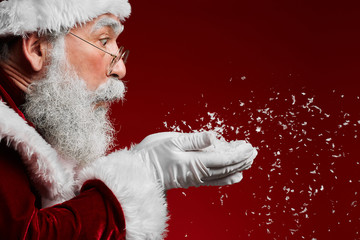 Side view portrait of classic Santa Claus blowing snow while standing against red background, copy space