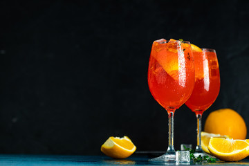 Two Aperol spritz cocktail in big wine glass with oranges, summer Italian fresh alcohol cold drink. Dark bar counter background with tools, summer mood concept, selective focus