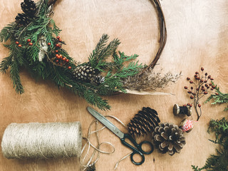 Christmas  rustic wreath on wooden table flat lay. Workshop of making modern christmas wreath. Pine branches, cones, scissors, twine on wooden table. Phone photo