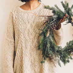 Girl in knitted sweater holding stylish rustic wreath. Hipster girl with rural modern wreath on white wall background. Festive decoration. Phone photo