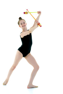 A girl gymnast performs exercises with a mace.