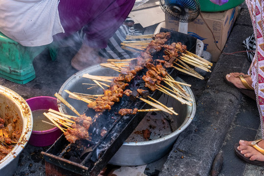 Tasty delicious chicken satay skewers being cooked on the footpath at the local Bali market
